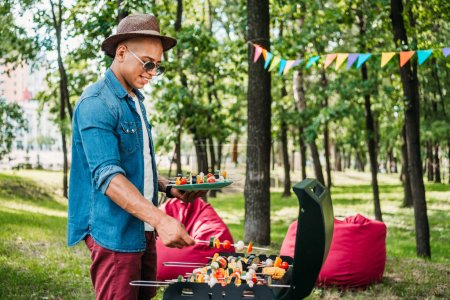 side view of smiling african american man taking grilled vegetables during bbq in park
