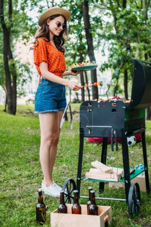 side view of smiling young woman taking vegetables from grill in park