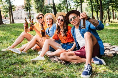 happy multiracial friends with beer resting on blanket in summer park