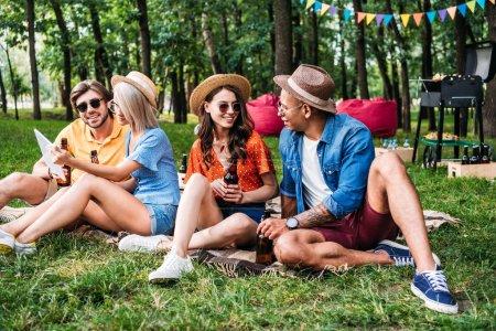 amigos interracial con cerveza y mesa descansando en el parque de verano