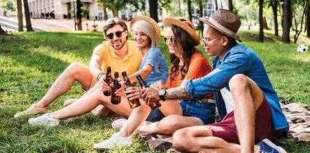 Photo pour Heureux amis multiraciales tinter les bouteilles de bière tout en reposant sur la couverture en parc d'été - image libre de droit