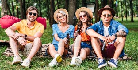 fröhliche multirassische Freunde mit Bier auf Decke im Sommerpark