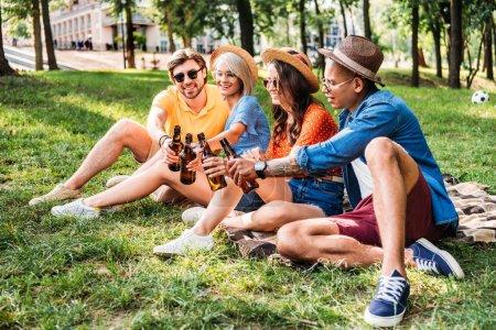 Photo pour Heureux multiracial amis cliquetis bouteilles de bière tout en se reposant sur la couverture dans le parc d'été - image libre de droit
