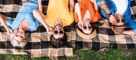 Photo pour Vue aérienne d'amis interracial dans lunettes de soleil reposant sur la couverture dans le parc - image libre de droit
