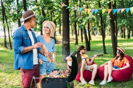 interracial young friends having barbecue in park on summer day