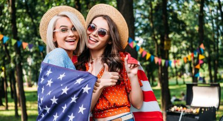 portrait of happy women with american flag in park