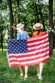 back view of friends with american flag walking in park
