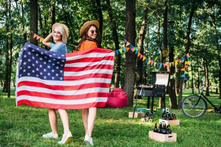 happy women in hats with american flag in park