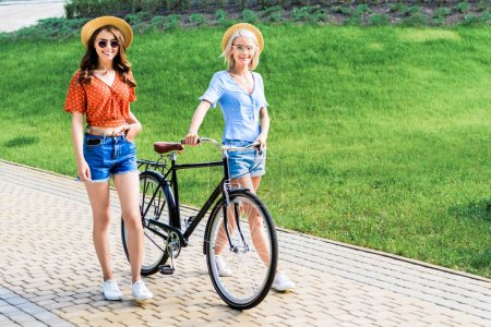 young smiling women in hats with bicycle walking on street