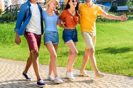 partial view of multicultural group of friends walking on street together on summer day