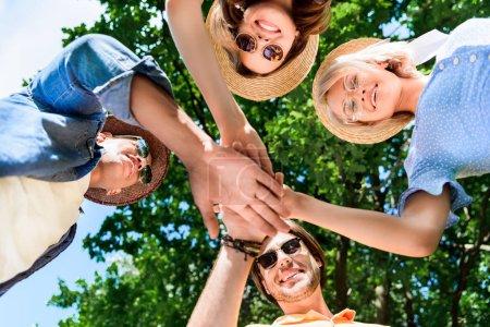 Foto de Vista inferior del multiétnicos amigos sonrientes cogidos de la mano juntos - Imagen libre de derechos