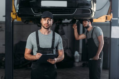 auto mechanic in overalls holding clipboard, while colleague working in workshop behind