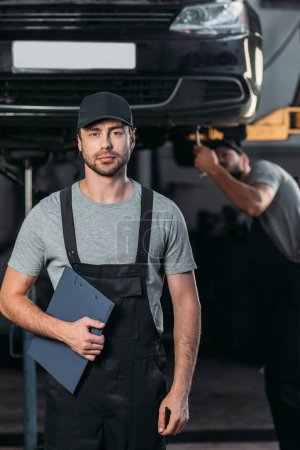 professional mechanic in overalls holding clipboard, while colleague working in workshop behind