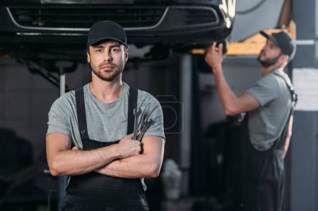auto mechanic posing in overalls with crossed arms, while coworker working in workshop behind