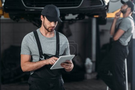 professional auto mechanic in overalls using digital tablet, while colleague working in workshop behind