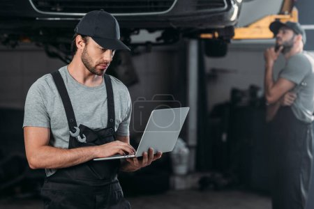 auto mechanic using laptop, while colleague working in workshop behind
