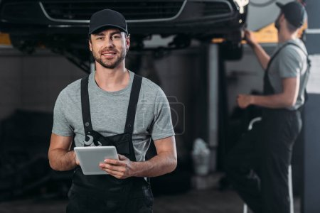 Photo for Happy mechanic in overalls using digital tablet, while colleague working in workshop behind - Royalty Free Image
