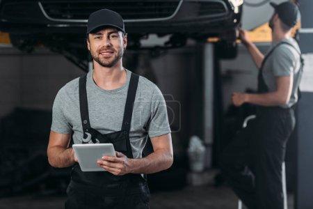 Foto de Feliz mecánico Overol uso de tableta digital, mientras que colega trabajando en taller detrás de - Imagen libre de derechos