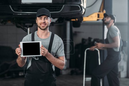 Photo for Auto mechanic holding digital tablet with blank screen, while colleague working in workshop behind - Royalty Free Image