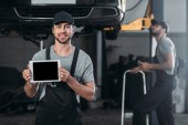 auto mechanic holding digital tablet with blank screen, while colleague working in workshop behind