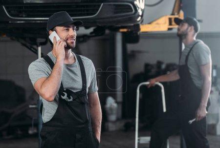 Photo pour Mécanicien automobile parler sur smartphone, et collègue de travail en atelier derrière - image libre de droit