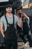auto mechanic showing smartphone with blank screen, while colleague working in workshop behind