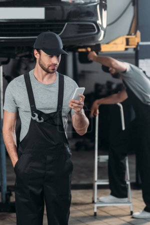 professional auto mechanic using smartphone, while colleague working in workshop behind