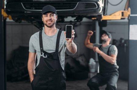 Foto de Mecánico automático que presenta teléfono inteligente con pantalla en blanco, mientras que el colega que trabaja en el taller detrás - Imagen libre de derechos