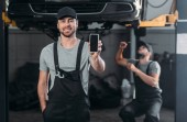 auto mechanic presenting smartphone with blank screen, while colleague working in workshop behind