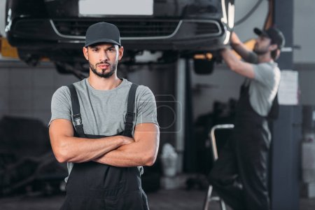 professional mechanic in overalls with crossed arms, while colleague working in workshop behind