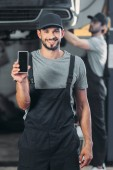 professional mechanic showing smartphone with blank screen, while colleague working in workshop behind