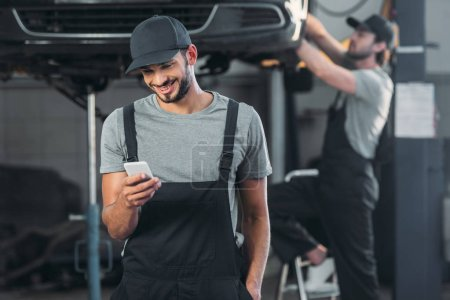 auto mechanic in overalls using smartphone, while colleague working in workshop behind