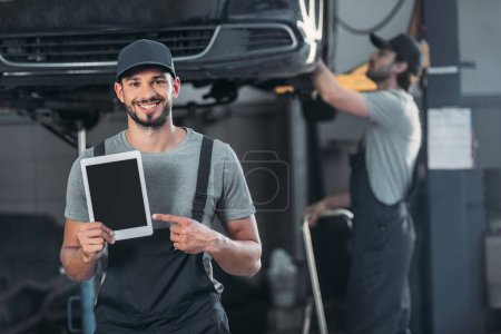 smiling mechanic showing digital tablet with blank screen, while colleague working in workshop behind