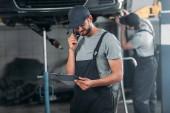 hablando mecánico en smartphone y buscar en el portapapeles, mientras que colega trabajando en taller detrás de