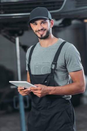 professional auto mechanic in overalls using digital tablet