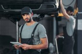 auto mechanic in overalls using digital tablet, while colleague working in workshop behind