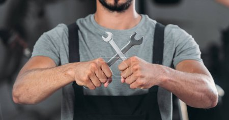 Photo for Cropped view of auto mechanic holding two wrenches - Royalty Free Image