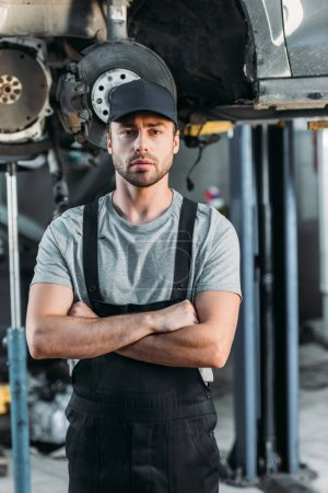 Photo for Serious mechanic posing with crossed arms in auto repair shop - Royalty Free Image