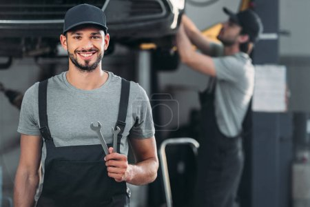 smiling auto mechanic holding wrenches, while colleague working in workshop behind