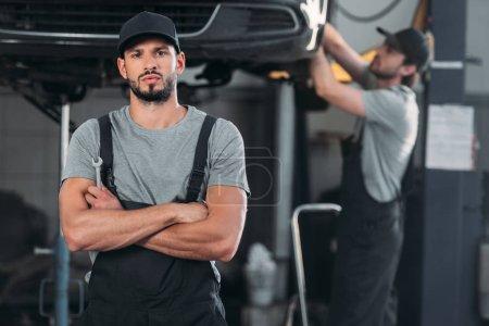 Photo pour Mécanicien sérieux avec les bras croisés, tenant une clé, et collègue de travail en atelier derrière - image libre de droit