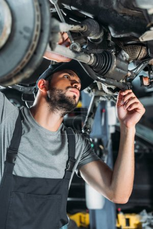 Photo for Professional engineer in overalls repairing car in mechanic shop - Royalty Free Image