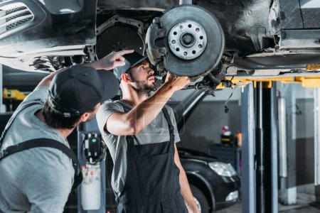 auto mechanics repairing car without wheel in workshop