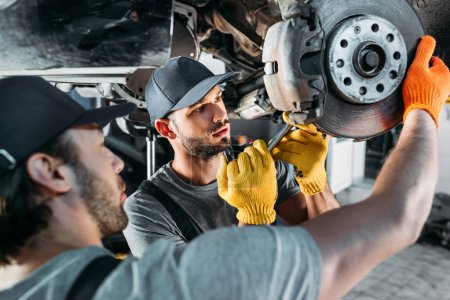 professional amle mechanics repairing car without wheel in auto repair shop