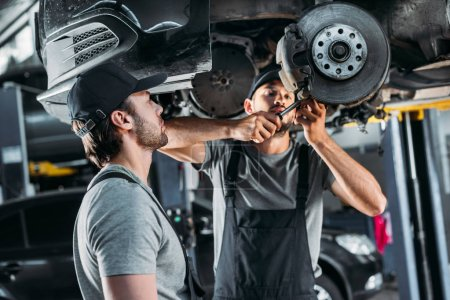 professional mechanics repairing car without wheel in auto repair shop