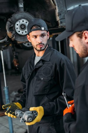 professional mechanics in uniform working with car and tools in workshop