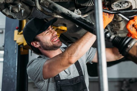 Photo for Professional mechanic in uniform repairing car in workshop - Royalty Free Image