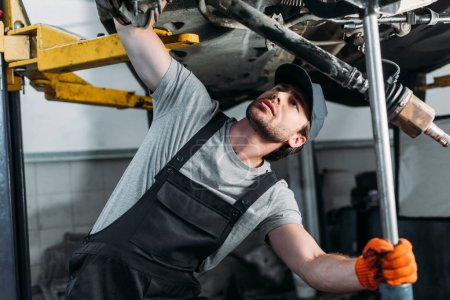 mechanic in uniform working with car in auto repair shop