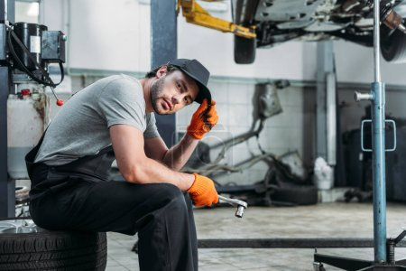 mechanic holding tool and sitting in auto repair shop