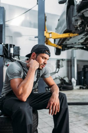 tired auto mechanic holding wrench and sitting in repair shop