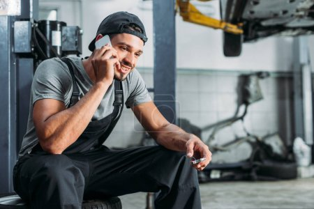 mechanic talking on smartphone and holding wrench in auto repair shop